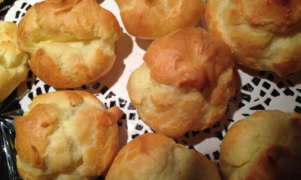 Our experience is that cream puffs shells actually do better the longer you allow them to dry. Best recommendation is to let them air dry at room temperature and then store them tightly covered in a dry container. The less moisture they are exposed to, the less likely they are to get soggy. You can also crisp them up/dry them a bit by placing them in a hot oven for a few minutes. Do not store in the refrigerator until you have filled them. Enjoy!