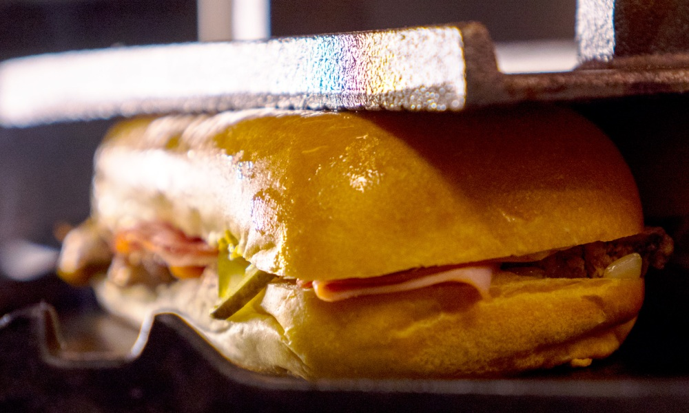 Our classic Cubano sandwich recipe, made famous in the Tampa Florida neighborhood of Ybor City, features mojo-marinated roast pork tenderloin with deli-sliced ham, Genoa salami and Swiss cheese, thin-sliced pickles and mustard- all layered on soft buttery Cuban rolls grill pressed flat and crispy.