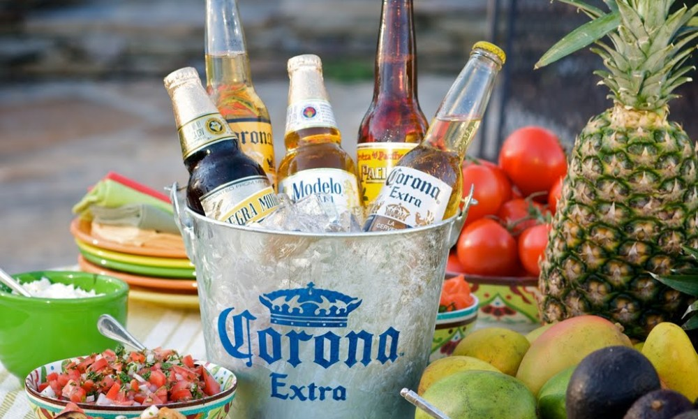 Photo depiction of a galvanized bucket, filled with ice, with several bottles of beer cooling inside.