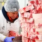 Butcher slicing steaks