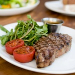 11 oz Grass-Fed Beef Ribeye with a side of roasted tomatoes watercress and sauce