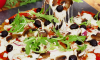 This pizza is made on the grill, then topped with barbecue sauce, cheese, olives and fresh arugula.