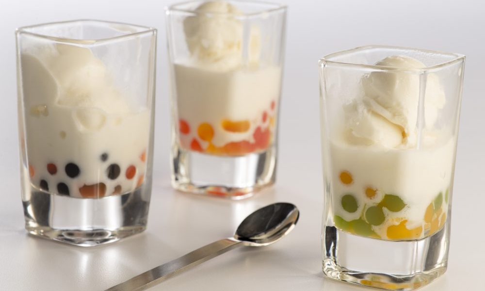 photo of glasses filled with ice cream, blended with boba flavored pearls and topped with cream