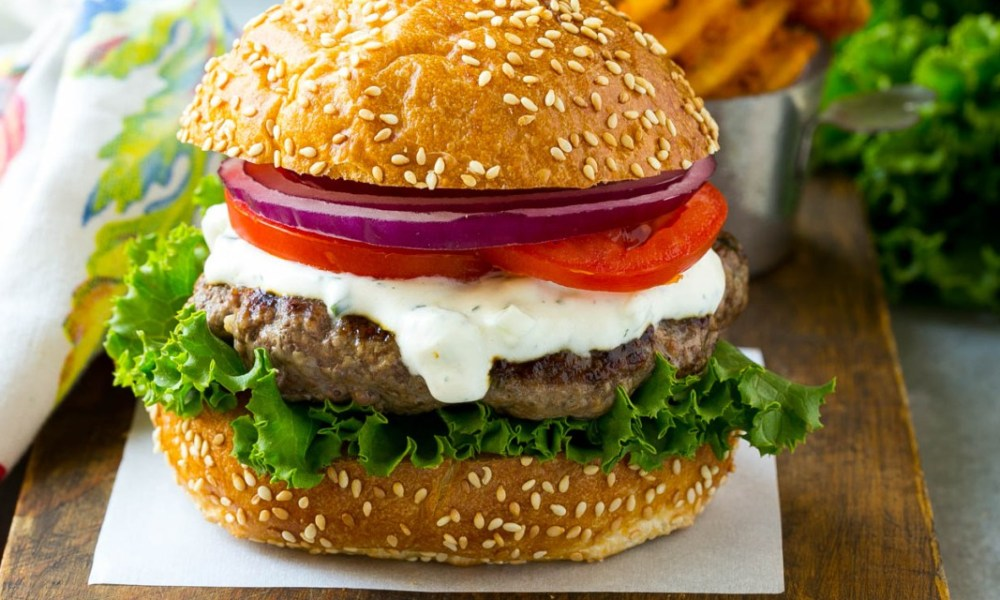 Photo depiction of a burger made with Australian lamb, Greek yogurt, lettuce, tomato and onion.