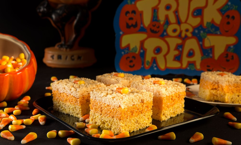 Photo of rice treats for Halloween displayed on a plate and surrounded by candy corn.