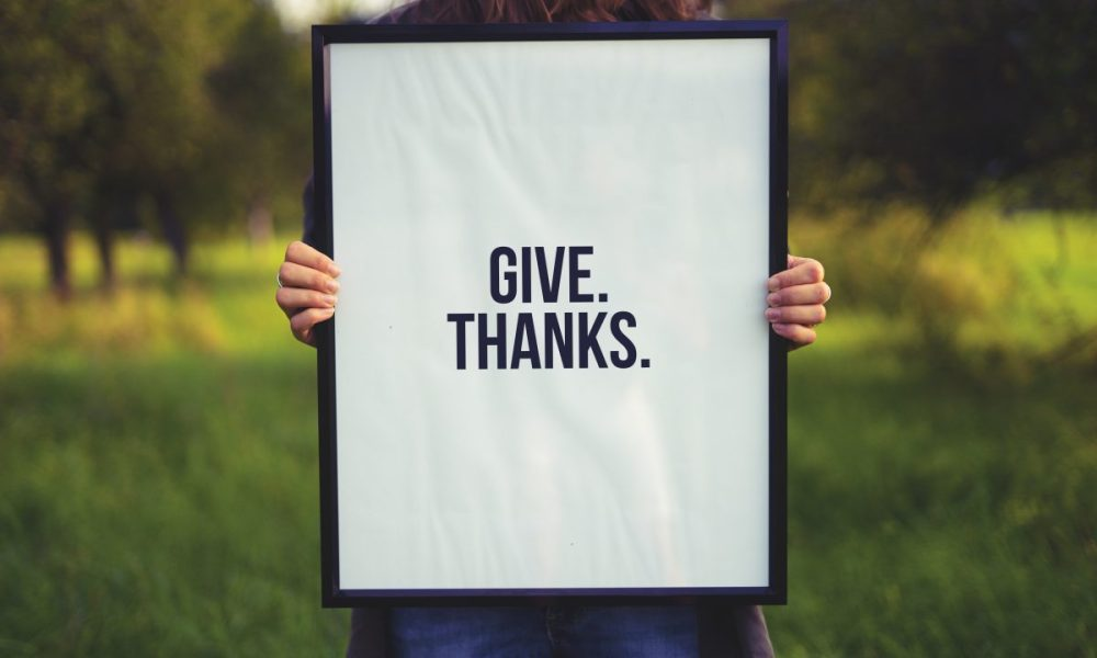 "A snapshot of a person holding a sign bearing the words ""Give Thanks."""