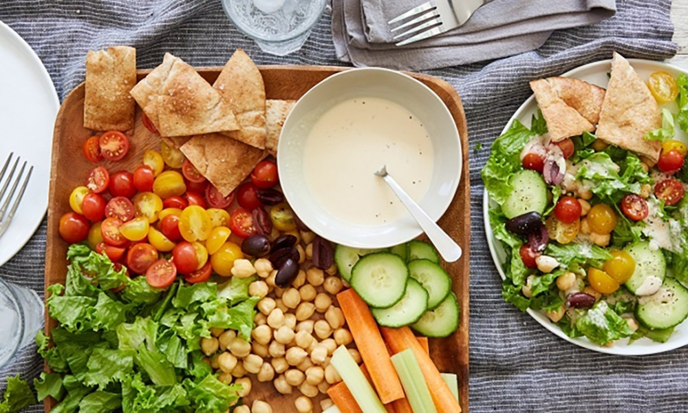 This colorful and tasty salad is a delicious combination of chickpeas, sweet tomatoes, cucumber, olives, carrots, celery, and pita chip,  served with a tangy hummus dressing! From start-to-finish, this salad only takes 15 minutes to create.