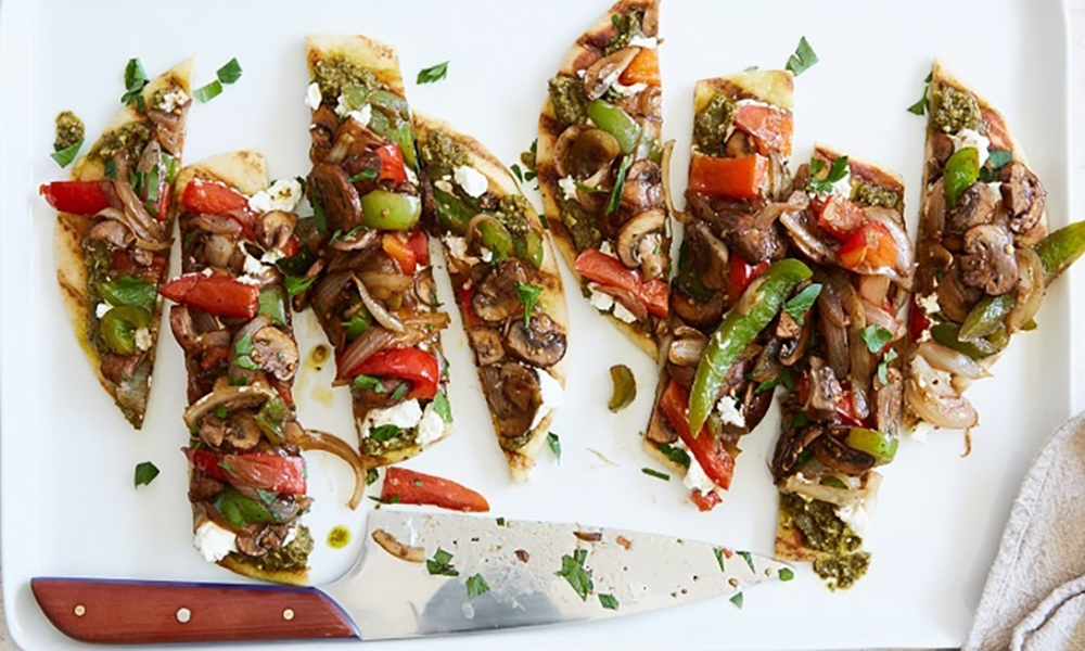 This delicious Pesto Goat Cheese Vegetable Flatbread is created with balsamic-seasoned peppers and mushrooms, a fresh pesto and creamy goat cheese atop a warm flatbread. It's the comfort food of your dreams and from start to finish only takes 20 minutes to make.