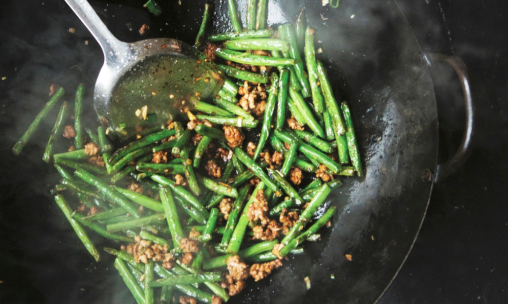 """A former coworker once scoffed at the idea that my dry-fried green beans could beat his broccoli salad at an office potluck party. Let's just say that I left the office with an empty dish, and he didn't. This recipe is Sichuanese in origin and involves blistering the green beans using a shallow frying method called gan bian, or ""dry-frying""."