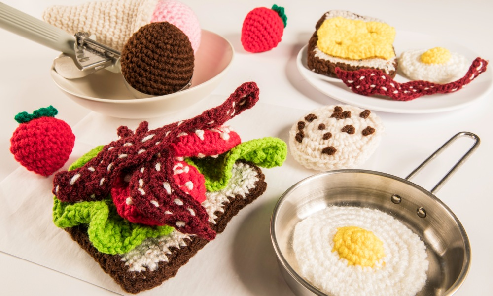 A table set with an assortment of crocheted food items. Whether used for teaching children about the foods they eat and how to prepare or simply to entertain your foodie friends, they're quite the unique foodie gift.