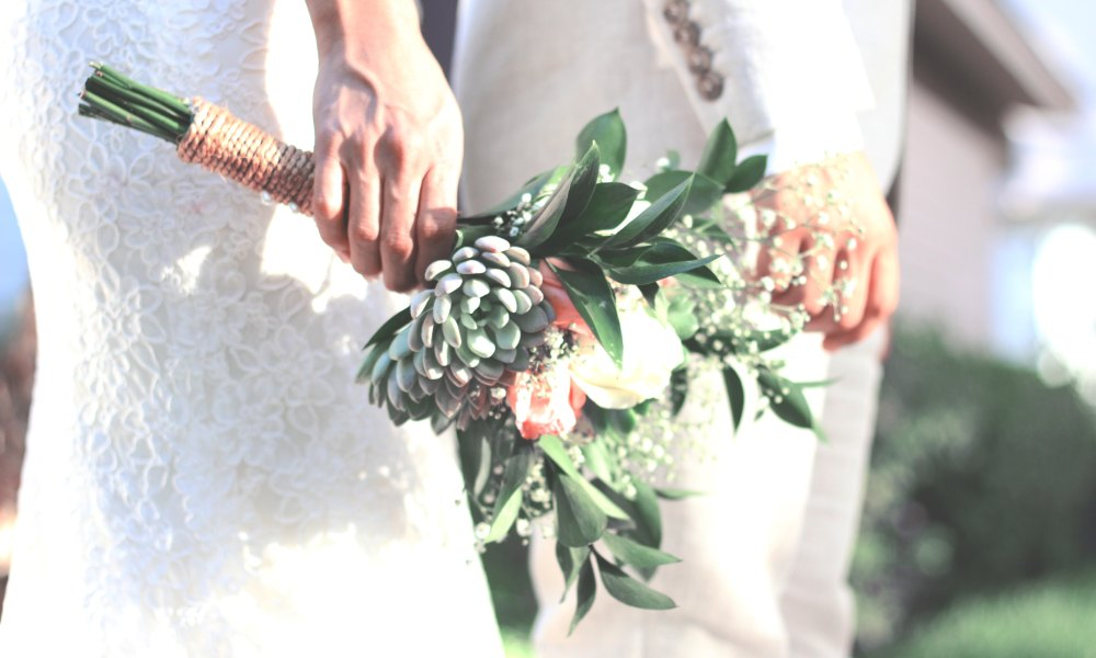 Shot of bride and groom's hand with the bride holding a bouquet.