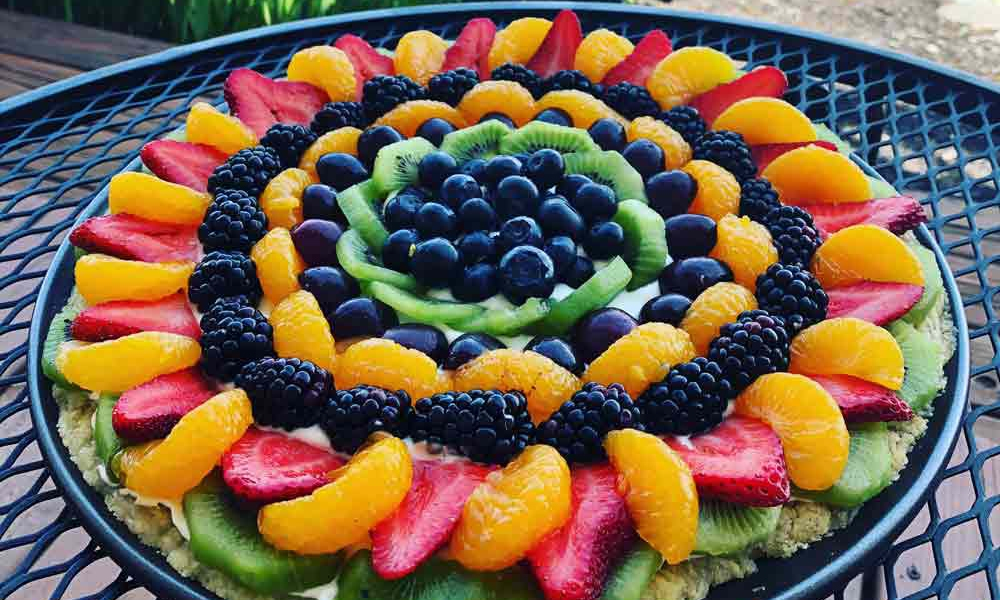 A beautiful nontraditional pizza made from fruit, layered upon a tart like crust.