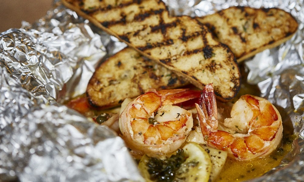 Grilled Frutti Di Mare Sauvignon Blanc, tomatoes, lemon-zested butter, basil, garlic and your choice of crustacean. Crusty ciabatta bread on the side.