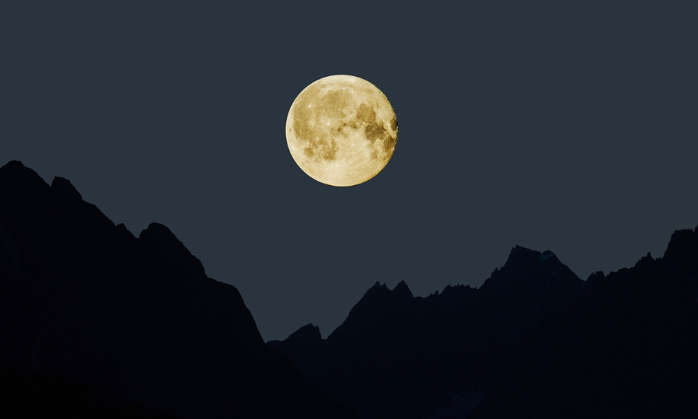 A full moon rises over the mountains.