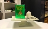 A copy of Joanne Flake's latest culinary mystery, Christmas Cake Murder sits atop an elevated cake stand next to a bowl of sugar.