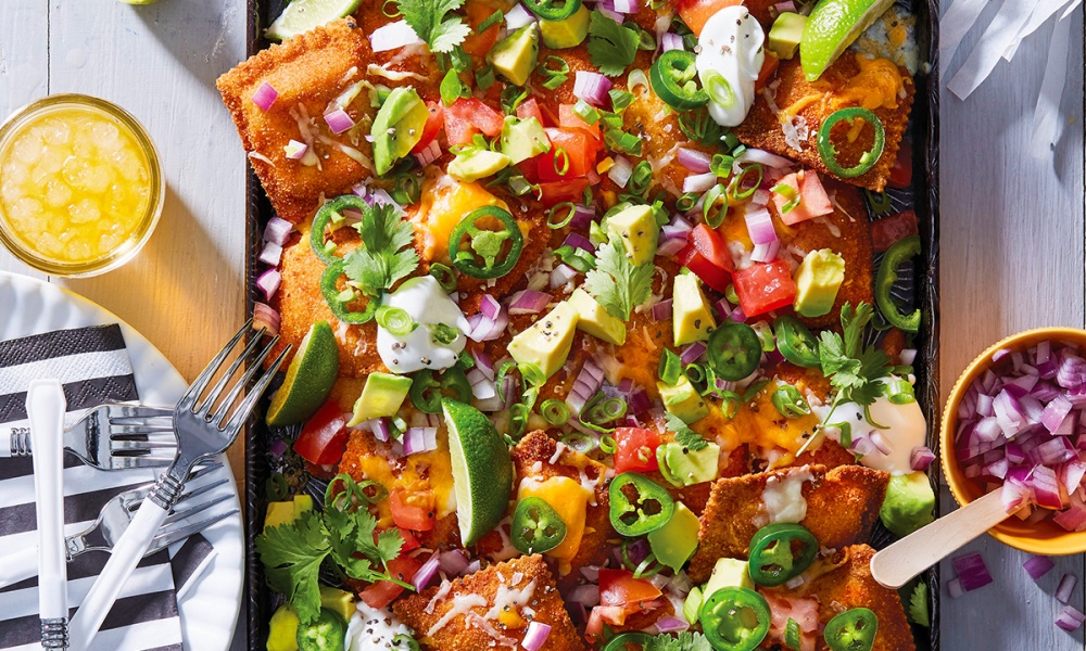 """A nontraditional take on the classic tailgate food, these """"nachos"""" are made with ravioli instead of tortilla chips. The breaded, fried, and baked preparation of the ravioli is original to St. Louis, making this a perfect dish to serve at (but not limited to) Missouri games. Piled with fresh toppings such as tomato, cilantro, avocado, and a creamy glaze, the cheesy goodness that results will have you blissfully swaying to the Marching Mizzou's """"Missouri Waltz."""""""