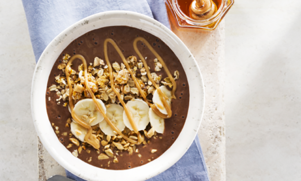 Start your day off right with this Chocolate Peanut Butter Banana Smoothie Bowl. It's a delicious breakfast smoothie in a bowl, made with bananas, chocolate almond milk, honey, peanut butter powder, cocoa powder and cocoa nibs. Then topped with a banana, granola, roasted peanuts and drizzled with peanut butter honey sauce.