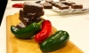 A stack of chocolate brownies on a cutting board next to fresh red and green jalapeno peppers.