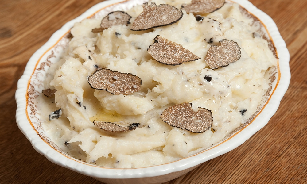 This recipe for Black Truffle Garlic Mashed Potatoes is inspired by the classic Joël Robuchon mashed potato recipe which calls for equal parts potato and butter. Garlic cloves slow-cooked in duck fat are added, along with a generous amount of black truffle butter for intensely earthy and rich potatoes.
