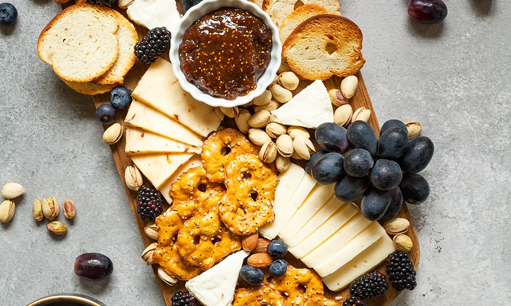 A spread of freshly sliced cheese and fresh fruit on a cutting board.