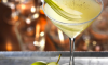 Photo of a pear vodka martini in an elegant martini glass, with the rim coated with sugar and the drink garnished with a fresh pear slice.