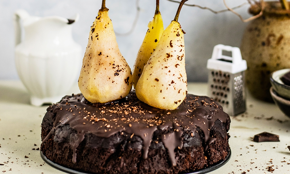 A chocolate cake topped with fresh pears to celebrate National Chocolate Cake day.