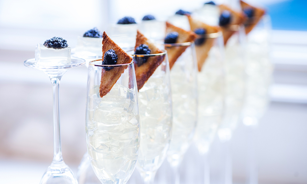 A row of champagne flute glasses with Jello caviar toast on the rims. Perfect for celebrating the Academy Awards.
