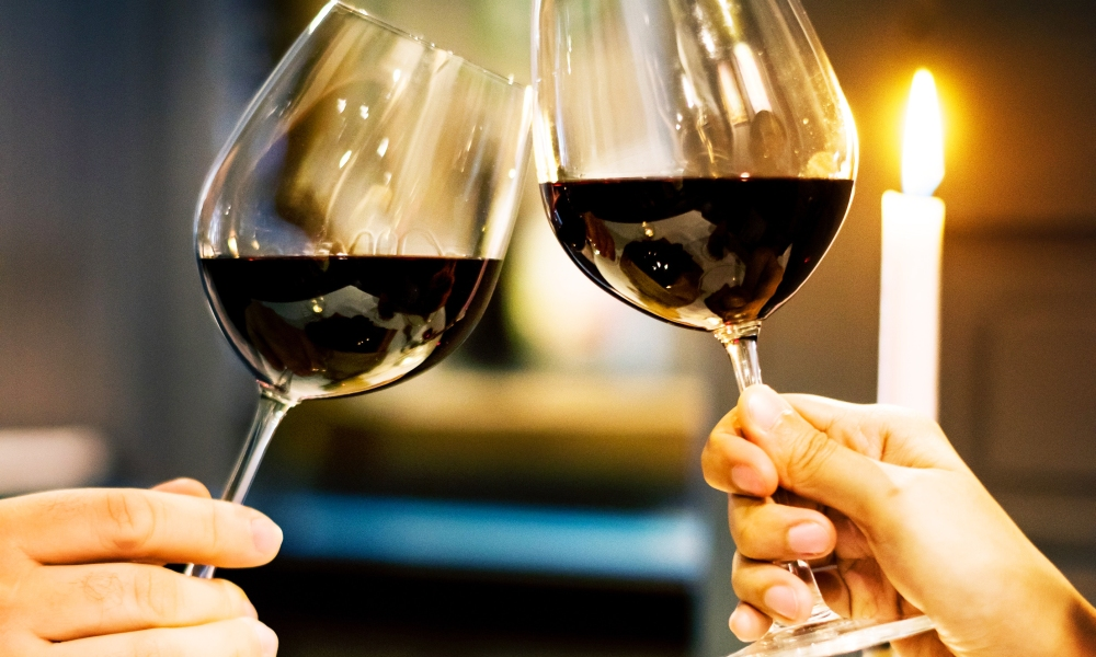 A couple toasts to Valentine's Day with two glasses of red wine.