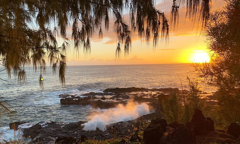 A beautiful sunset as the waves crash onto the beach at Spouting Horn, Kaua'i.