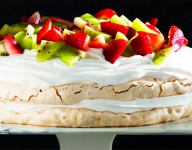 Pavlova topped with Whipped Cream and Fruit