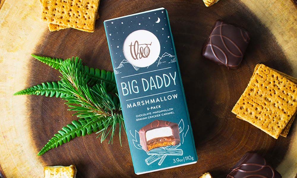 A Big Daddy marshmallow treat which is handmade graham cracker crust, a layer of buttery vanilla infused caramel and a fluffy marshmallow cloud on top, then enrobed in dark chocolate, and decorated with an alderwood smoked milk chocolate flourish.